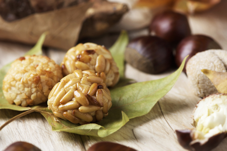 closeup of some chestnuts, some panellets and a roasted sweet potato, as a typical snack eaten in All Saints Day in Catalonia, Spain, called castanada, and some autumn leaves on a wooden table