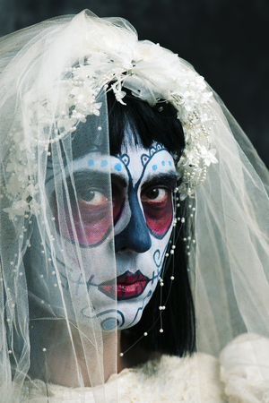 closeup of a bride with a mexican calaveras makeup, wearing diadem and veil, against a dark background