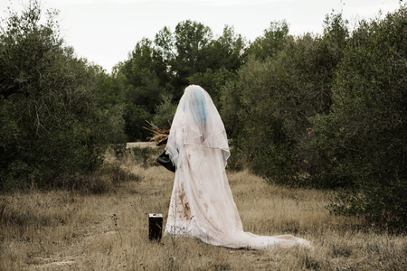 a scary bride with long blue hair wearing a dirty and ragged wedding dress, and holding a bridal bouquet with wilted flowers and an old purse, seen from behind, in a disturbing rural landscape at dusk