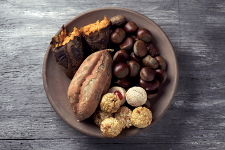 high-angle shot of an earthenware bowl with some chestnuts, some panellets and a roasted sweet potato, as a typical snack eaten in All Saints Day in Catalonia, Spain, called castanada, on a table