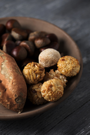 closeup of an earthenware bowl with some chestnuts, some panellets and a roasted sweet potato, as a typical snack eaten in All Saints Day in Catalonia, Spain, called castanada, on a wooden table