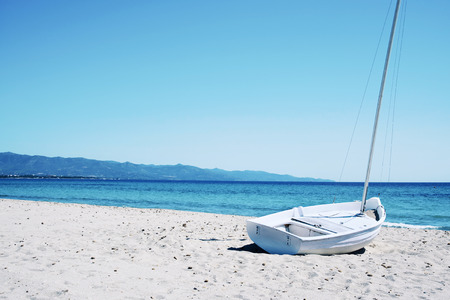 a sailboat stranded in the white sand of the Spiaggia del Poetto beach in Cagliari, Sardinia, Italy
