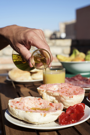 closeup of a man preparing a typical catalan pa amb tomaquet, bread with tomato, dressing with olive oil the two halves of a bun placed on a plate on a wooden table outdoors
