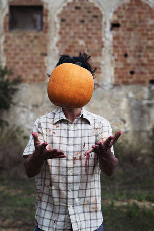 closeup of a scary man wearing ragged and dirty clothes with blood stains throwing a pumpkin up in the air in front of an abandoned house