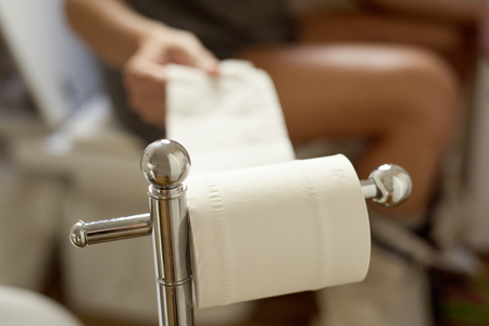 closeup of a young caucasian man in the toilet taking some paper from the roll