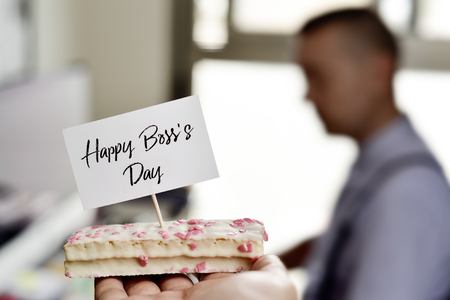 someone holding a piece of cake with a signboard with the text happy boss day written in it next to a desk, where there is a man working in a computer