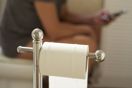 a young caucasian man using his smartphone in the toilet while sitting in the bowl, with a roll of paper placed in a toilet paper holder in the foreground