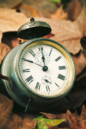 closeup of an old and rusty alarm clock surrounded by dry leaves, depicting the end of the summer time and the beggining of autumn