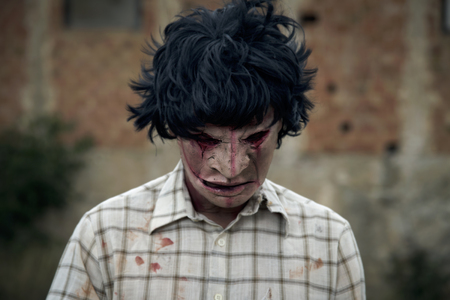 closeup of a scary disfigured man looking down wearing a ragged and dirty shirt with stains of blood, in front of an abandoned house