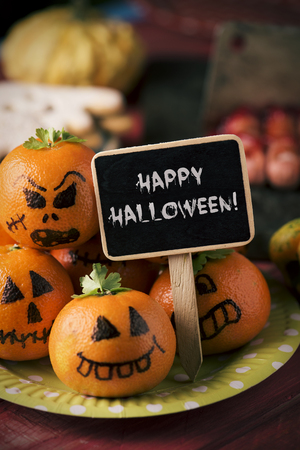 closeup of some funny food, such as tangerines as carved pumpkins with funny faces, hotdogs in the shape of bloody fingers and a black signboard with the text happy halloween written in it