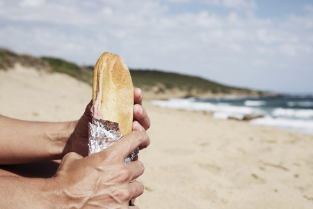carnes: closeup of a young caucasian man eating a ham and cheese sandwich on the beach