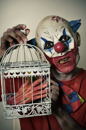 closeup of a scary evil clown with a bloody amputated hand in a birdcage Stock Photo