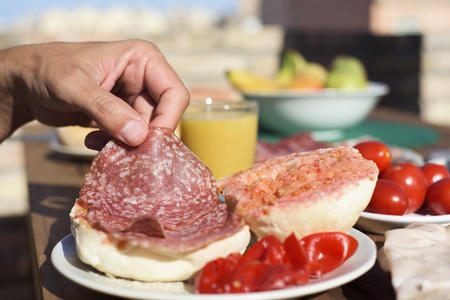 closeup of a man preparing a sandwich in a bun with typical catalan pa amb tomaquet, bread with tomato, stuffed with salami, on a wooden table outdoors
