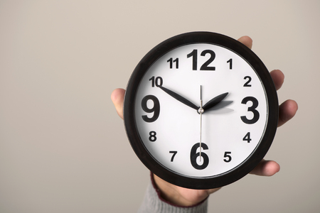 closeup of the hand of a young caucasian man holding a clock which is being adjusted backward or forward one hour at the end or at the beginning of the summer