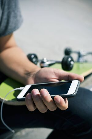 closeup of a young caucasian man outdoors with a skateboard on his lap using his smartphone with earphones plugged to it