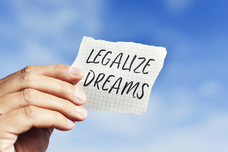 closeup of the hand of a young caucasian man holding a pieces of paper with the text legalize dreams written in it, against the sky Banque d'images