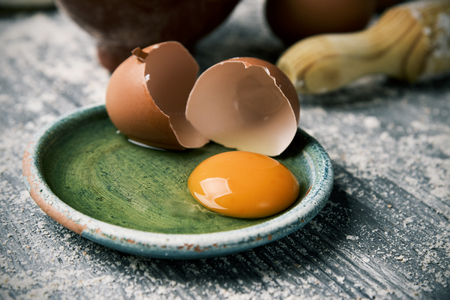 closeup of a cracked egg in a green plate and a wooden rolling pin on a rustic table sprinkled with flour