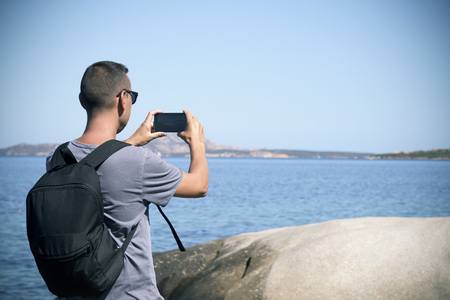 closeup of a young caucasian man with a backpack seen from behind taking a picture, with his smartphone, of the Mediterranean sea at Cala Ginepro beach, in the Costa Smeralda, Sardinia, Italy Banque d'images