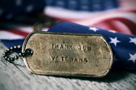 Close-up van een roestige hond tag met de tekst dank u veteranen gegraveerd in het, naast een vlag van de Verenigde Staten, op een rustieke houten oppervlak Stockfoto - 89751270