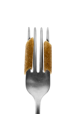 two uncooked buckwheat penne rigate in the tines of a fork, on a white background