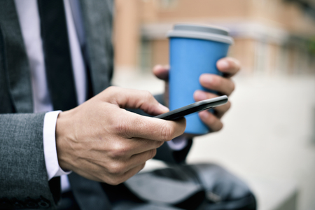 closeup of a young caucasian businessman in a gray suit using a smartphone and having a coffee outdoors