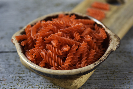 closeup of an earthenware bowl full of uncooked red lentil fusilli on a gray rustic wooden table