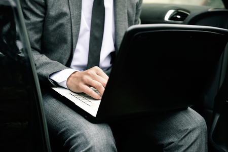 closeup of a young caucasian businessman in a gray suit using a laptop sitting at the back seat of a car Banque d'images