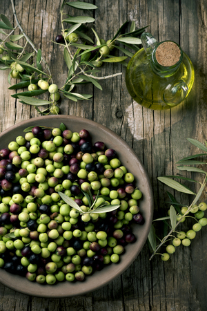 high-angle shot of an earthenware bowl full of arbequina olives from Catalonia, Spain, a cruet with olive oil and some twigs of olive tree on a wooden rustic table Banque d'images