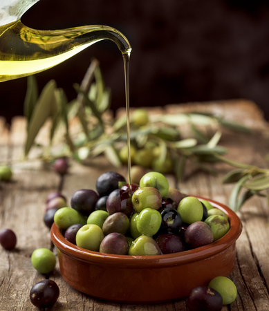closeup of an earthenware bowl full of arbequina olives from Catalonia, Spain, a cruet with olive oil and some twigs of olive tree on a wooden rustic table