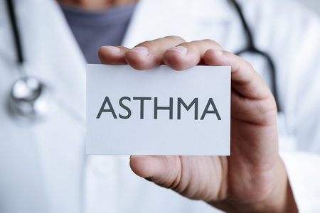 closeup of a young caucasian doctor man in a white coat showing a signboard with the text asthma written in it