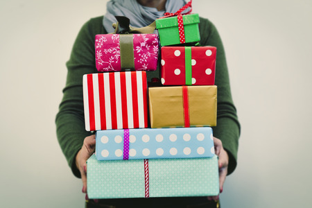 closeup of a young caucasian woman holding a pile of gifts in her hands wrapped in nice papers and tied with ribbons of different colors