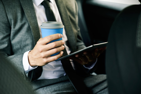 closeup of a young caucasian businessman in a gray suit using a digital tablet and having a coffee sitting at the back seat of a car