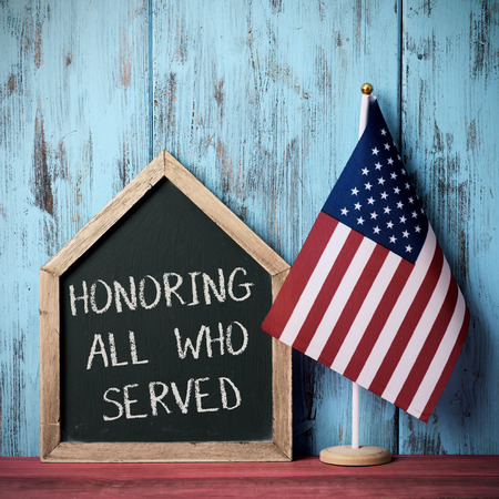 the text honoring all who served written in a house-shaped chalkboard and a flag of the United States, against a blue rustic wooden background