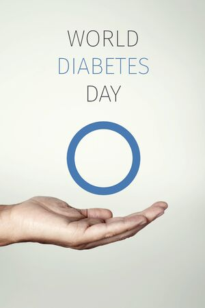 text world diabetes day and a blue circle, symbol of diabetes, in the hand of a young man