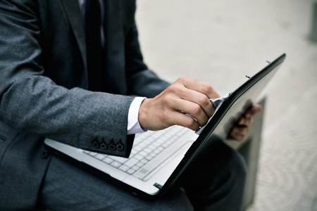closeup of a young caucasian businessman in a gray suit cleaning the screen of a laptop with a microfiber cloth sitting outdoors