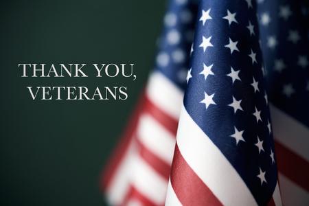 einige amerikanische Flaggen und der Text danken Ihnen Veteranen gegen einen dunkelgrünen Hintergrund