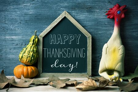 a house-shaped blackboard with the text happy thanksgiving day written in it, a funny rubber plucked turkey, some autumn leaves and some pumpkins against a rustic wooden surface