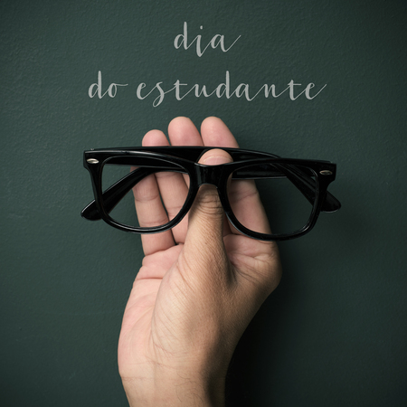 a pair of black plastic-rimmed eyeglasses in the hand of a young man and the text dia do estudante, students day in portuguese, against a green chalkboard