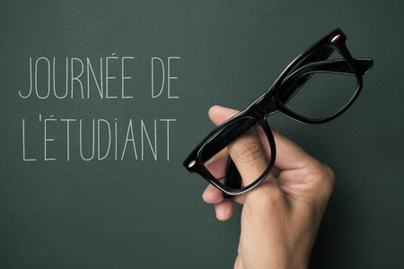 a pair of black plastic-rimmed eyeglasses in the hand of a young man and the text journee del etudiant, students day in french, against a green chalkboard