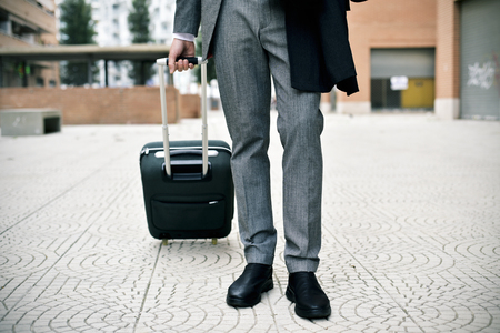 closeup of a young caucasian businessman in an elegant gray suit pulling a trolley by its handle in a pedestrian zone Banque d'images