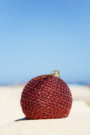 closeup of an elegant red christmas ball in the sand of a beach with the sky in the background and a large blank space on top