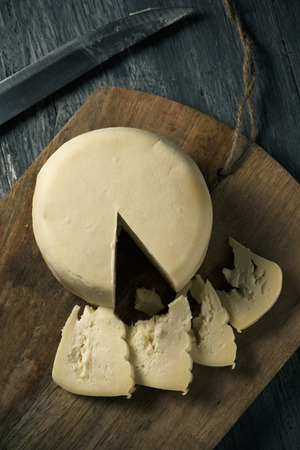 a Spanish Arzua-Ulloa cheese, a typical cow cheese from Galicia, on a wooden chopping board, placed on a rustic wooden table