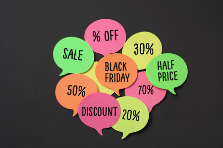 text black friday in an orange speech bubble and some other speech bubbles of different colors with different percentages of discount, against a dark gray background