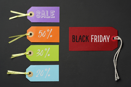 text black friday in a red paper label and some other paper labels of different colors with different percentages of discount, against a dark gray background