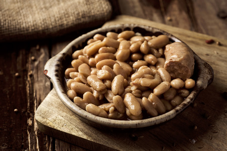 closeup of an earthenware bowl with a cassoulet de Castelnaudary, a typical bean stew from Occitanie, in France, on a rustic wooden table Banque d'images