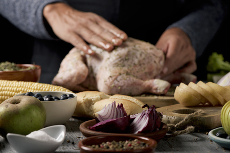 closeup of a young caucasian man preparing a turkey placed on a rustic wooden table full of ingredients to stuff it such as apple, onion or different spices, and celery or a roast corn on the cob