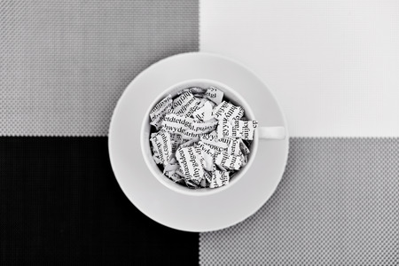 a printed letter or document broken into a thousand pieces in a white ceramic coffee cup placed on a black, gray and white background Stock Photo