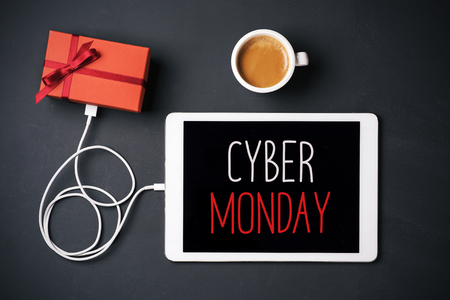 high-angle shot of a tablet with the text happy cyber monday in its screen, connected to a gift by a cable, and a cup of coffee, placed on a dark gray surface