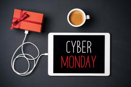 high-angle shot van een tablet met de tekst happy cyber maandag in het scherm, verbonden met een cadeau door een kabel en een kopje koffie, geplaatst op een donkergrijs oppervlak