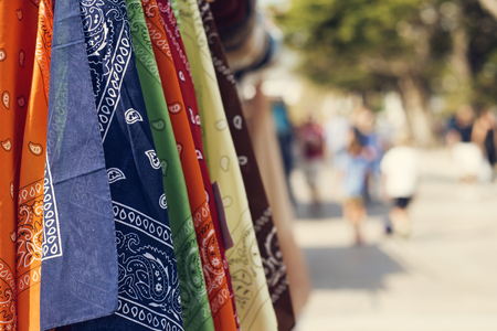 some paisley patterned kerchiefs of different colors on sale hanging on a rack in the street
